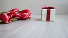 Gift box enters the frame to the colors, and then hand picks up a gift. Stock Footage