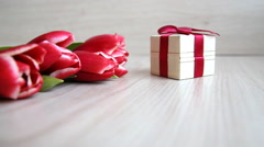 Tulips lay down next to the gift box with a red bow Stock Footage