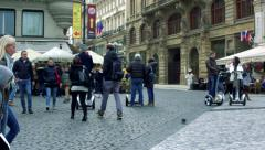 Slowmotion view to centre of town where people walk and go on Segway Stock Footage