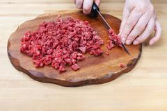 woman finely chops meat on cutting board - stock photo