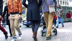 Slowmotion man and woman with pram who wait on sidewalk in front of stand Stock Footage