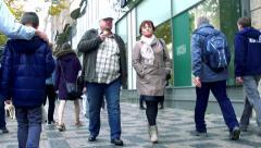 Slowmotion people walk on sidewalk in street along the shops. Stock Footage