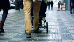 Slowmotion man and woman with pram walk in street in town Stock Footage
