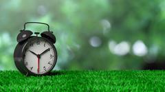 Retro alarm clock on grass with abstract green bokeh background Stock Illustration