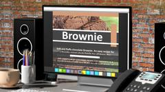 Monitor with Brownie recipe on desktop with office objects. - stock illustration