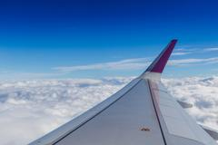 Blue horizon and white clouds. Aerial shot with airplane wing - stock photo