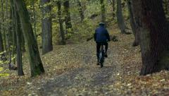 Slowmotion cyclist goes on bike na path in forest Stock Footage