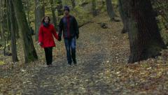 Slowmotion people (couple) walk on trail in forest Stock Footage