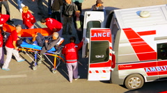 Emergency doctors putting a man on the wheelchair in the ambulance car Stock Footage