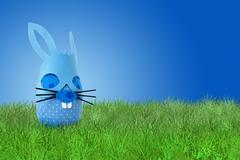 Funny Easter blue bunny on grass Stock Photos
