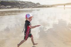 A child in a wetsuit running on sand Stock Photos