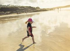 A child in a wetsuit and sunhat running on sand Stock Photos