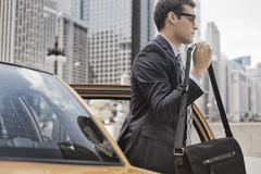 Businessman in a work suit with a computer bag getting out of a taxi. Stock Photos