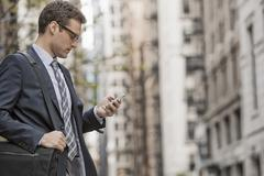 A working day. Businessman in a work suit on a city street, using his phone. - stock photo