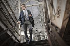Businessman in a work suit and tie walking down stairs in a public space. - stock photo
