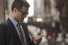 Businessman in a work suit and tie on a city street, looking at his phone. - stock photo