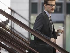 Businessman in a work suit and tie walking down steps holding a cup of coffee. - stock photo