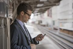 Businessman in a work suit and tie on a station platform, checking his phone, - stock photo