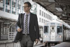 Businessman in a work suit and tie on a railway station platform. Stock Photos