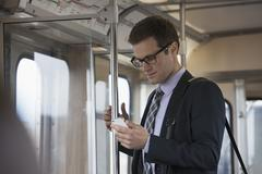 Businessman in a work suit and tie in a train carriage, checking his phone. - stock photo