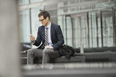 Businessman in a work suit and tie sitting checking his phone. - stock photo