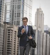 Businessman in a work suit and tie on a city street, checking his phone. - stock photo