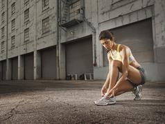 A woman runner leaning down and tying her running shoes laces. - stock photo