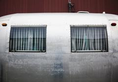 The side of an aluminum trailer with two windows. An Airstream shape. - stock photo