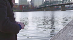 Closeup slow-mo view of man skipping rocks from a dock by a bridge in city Stock Footage