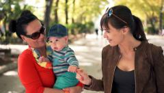 Two happy girlfriends with small child walking in the park in th city Stock Footage