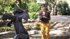 Young woman looking at sculpture in city park and reading about it in guide Stock Footage