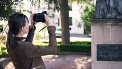 Woman taking photo of sculpture in city park Stock Footage