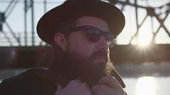 Slow-mo portrait of stylish man wearing sunglasses by a city bridge at sunset Stock Footage