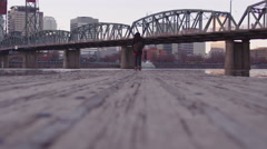 Classy dressed walks from edge of dock by a bridge in the city toward camera - stock footage