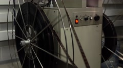 Dolly shot of big rotating reels in pro cinema projector, 4K video, part of set Stock Footage