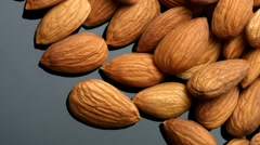 Almonds over black background Stock Footage