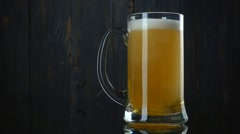 Glass of beer over dark wooden background. Slow motion Stock Footage