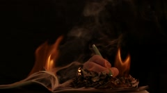 Mans hand writing over the fire on book slow motion on black background Stock Footage