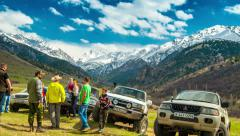 4K Timelapse. A column of cars and people at the foot of the mountains Stock Footage