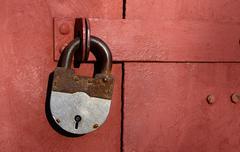 Closeup of old lock on red metal garage door Stock Photos