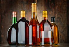 Glass and bottles of assorted alcoholic beverages. Stock Photos