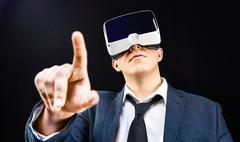 Businessman uses Virtual Reality VR head-mounted display - stock photo