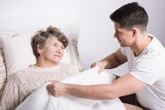 Covering grandmother with blanket Stock Photos