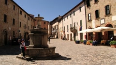 People walk by the central square of the medieval town of San Leo, Italy. Stock Footage