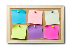 Blank post it notes on a cork notice board - stock photo