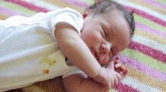 Newborn lies on his back on blanket - stock footage