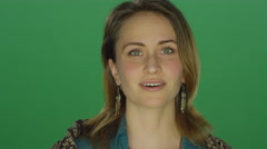 Young woman looks happily surprised, on a green screen background Stock Footage