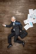 Top view photo of senior businessman on wooden floor - stock photo