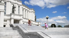 The girl rolls a pedestal near Theatre of Belarus Stock Footage