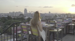 Woman in a rooftop restaurant, ungraded, slog2 Stock Footage
